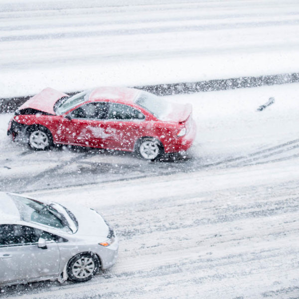 A car crashed on the side of the road in a snow storm