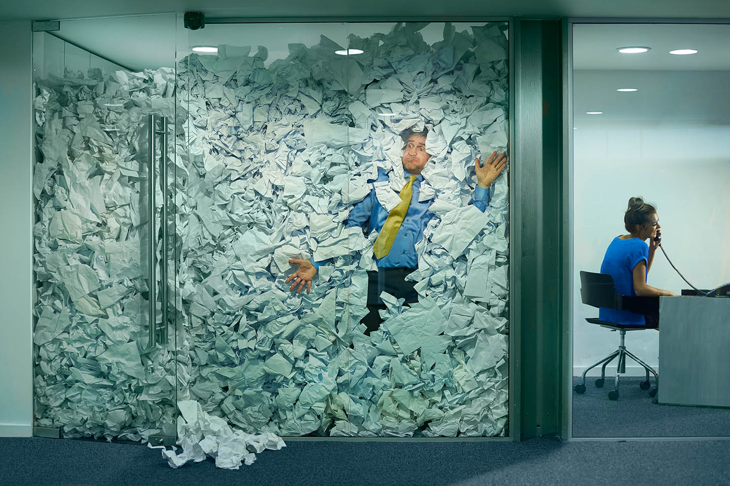 A man squished against a glass wall by a mountain of crumpled paper