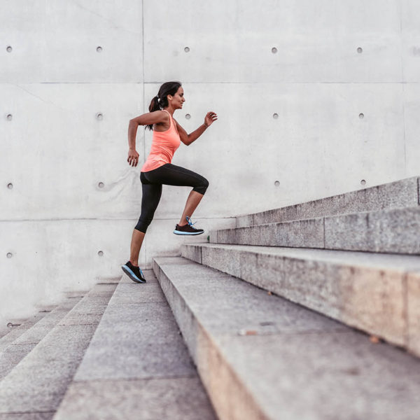 A woman running up concrete stairs