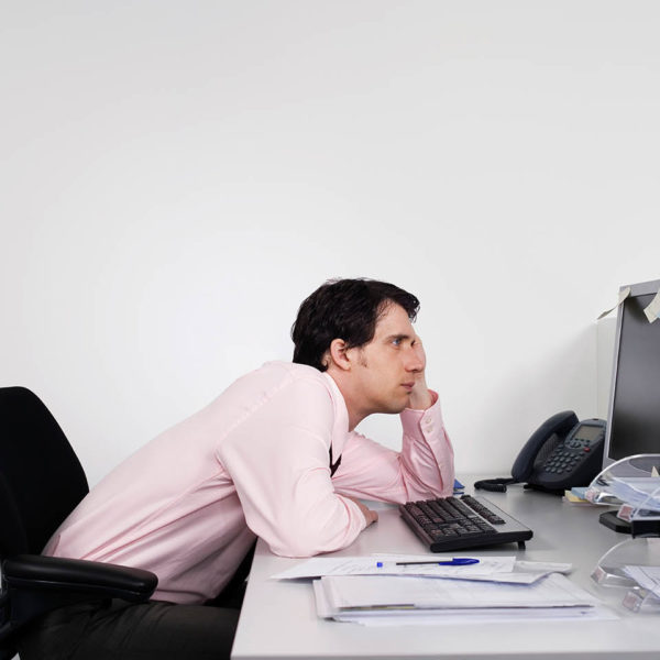 A bored looking man slouching at his desk