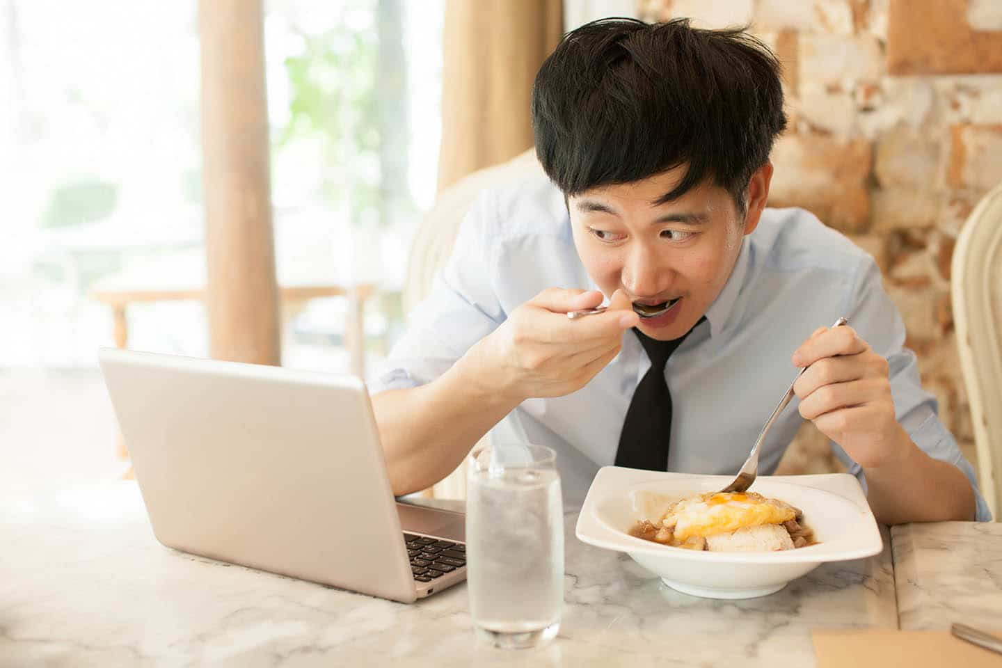 A man eating food while looking at a computer
