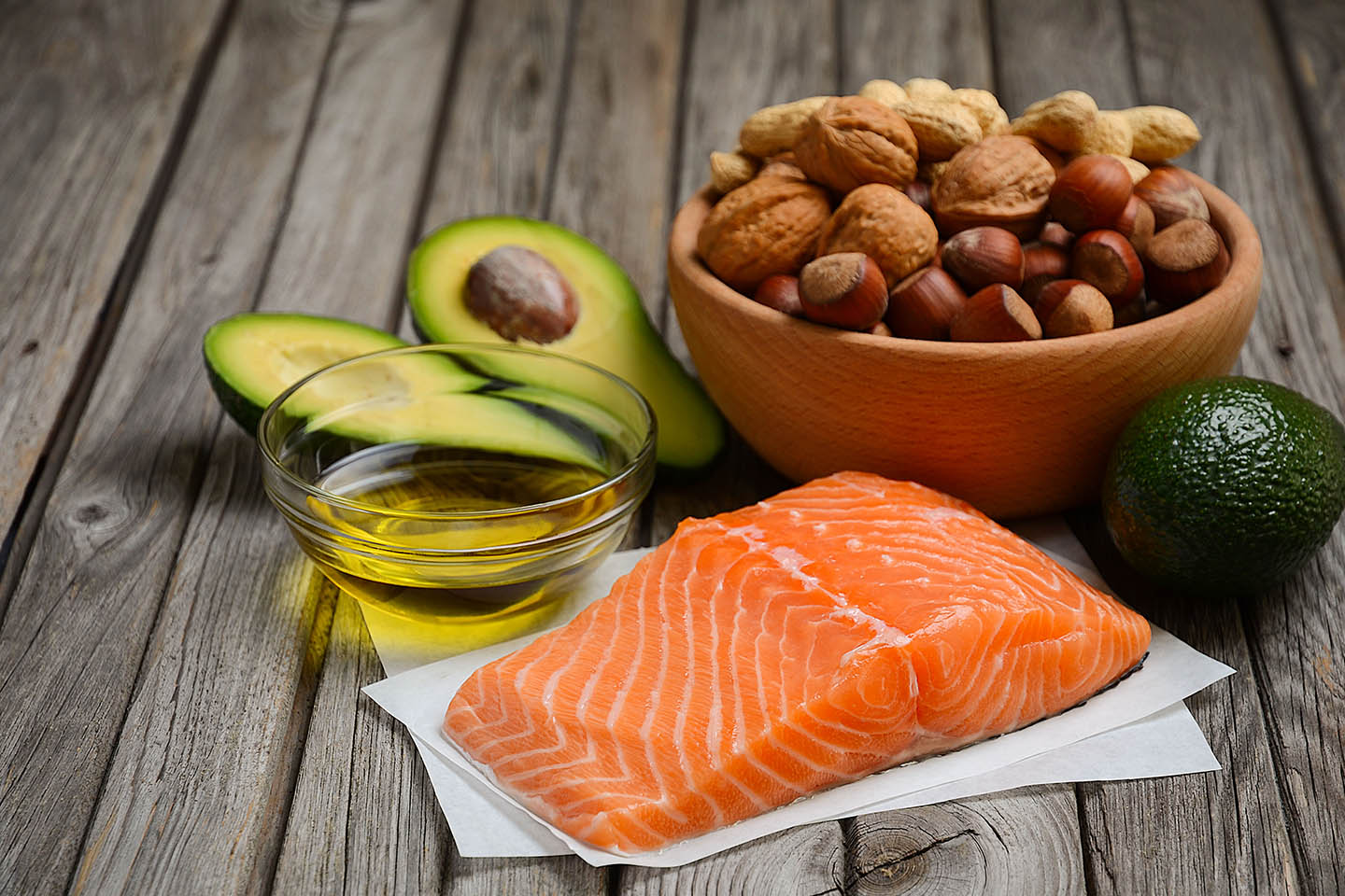 A piece of salmon, avocado, nuts, and a bowl of oil