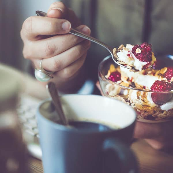 A bowl of yogurt, granola, and berries, with a cup of coffee