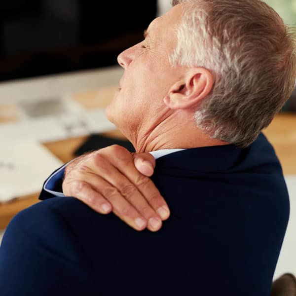 A man rubbing the back of his shoulder