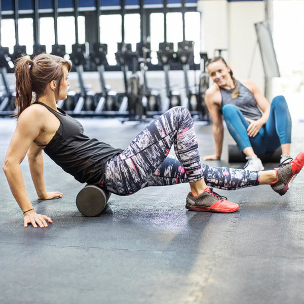 Two women using foam rollers to stretch in a gym