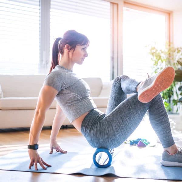 A woman stretching using a foam roller