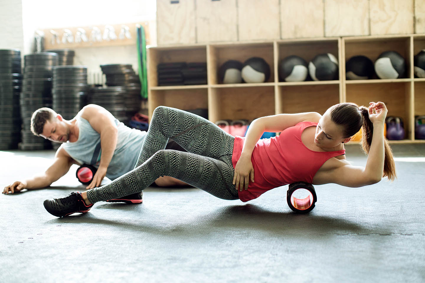 A woman and man using foam rollers in the gym