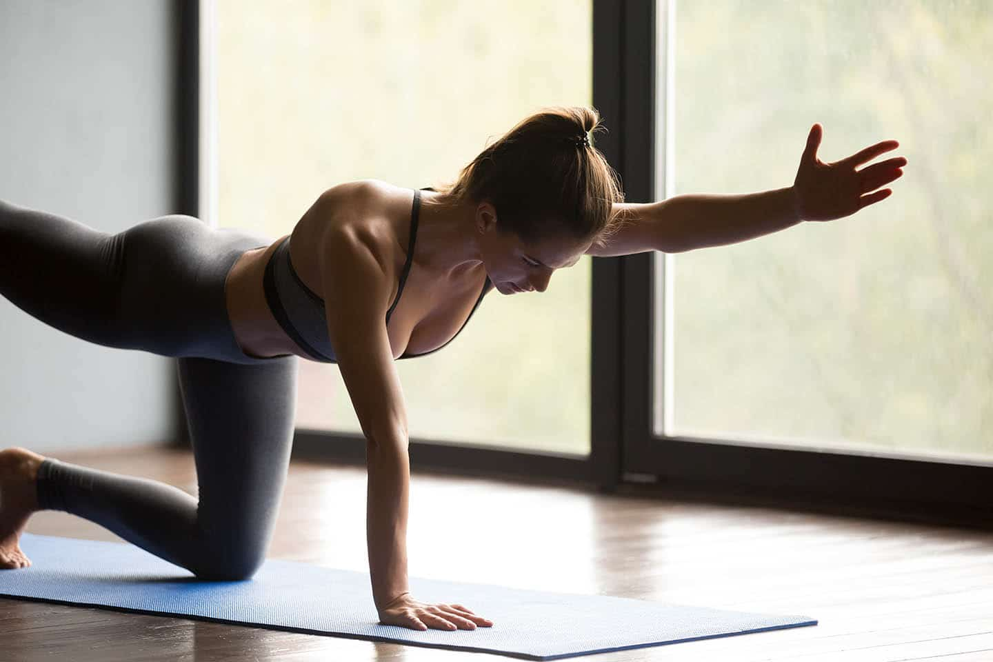 A woman wearing athletic clothes stretching on a mat
