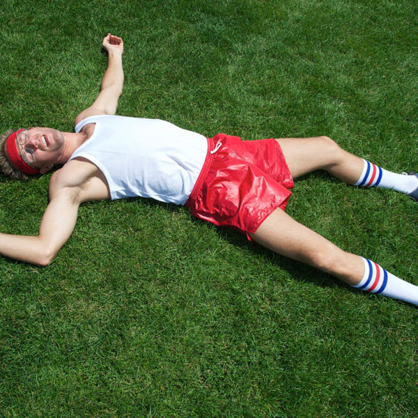 A exhausted man passed out in the grass.