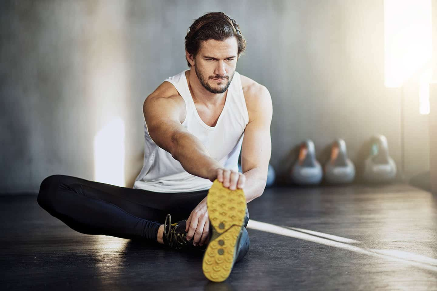 A fit man stretching in the gym