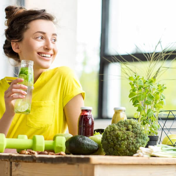 A smiling woman enjoying a healthy beverage