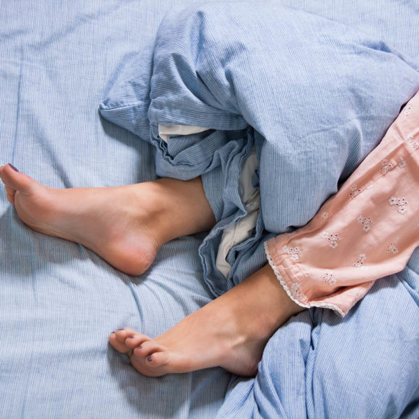 A woman's feet sticking out from under bed sheets