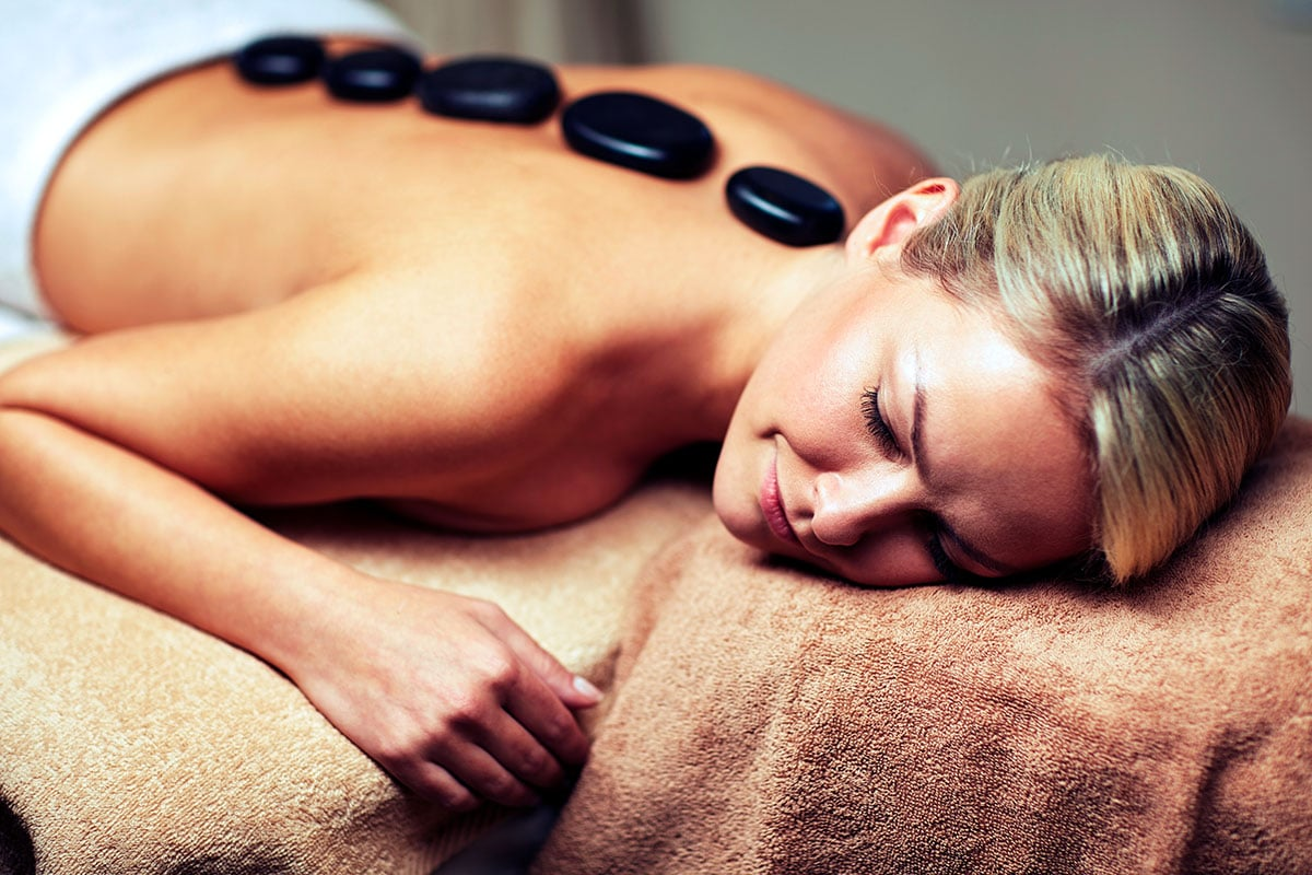 A woman lying on a massage table, receiving a hot stone therapy treatment