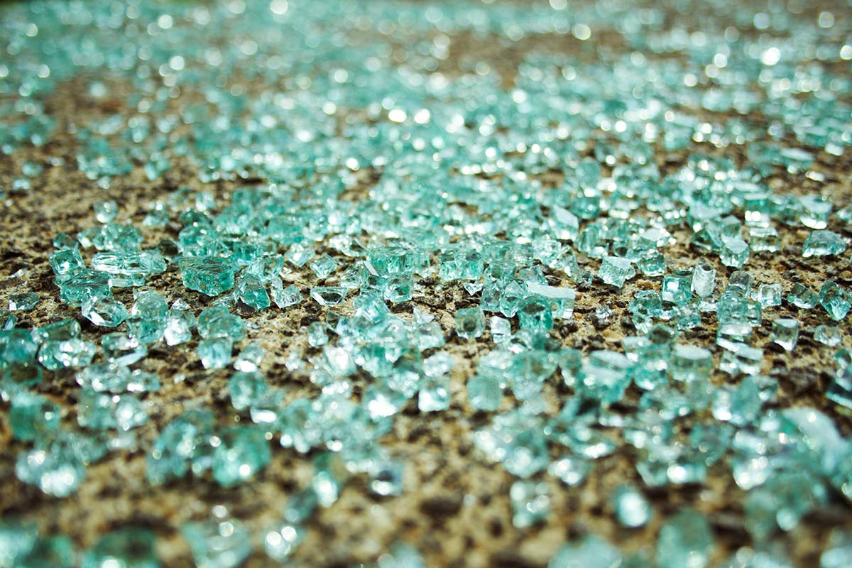 Broken glass on pavement after a motor vehicle accident