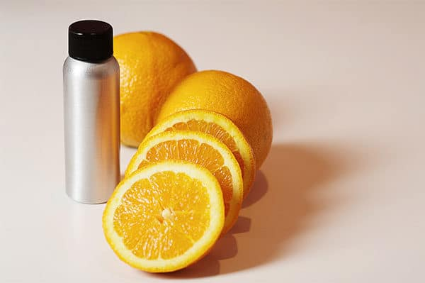 Bottle of orange oil and orange slices