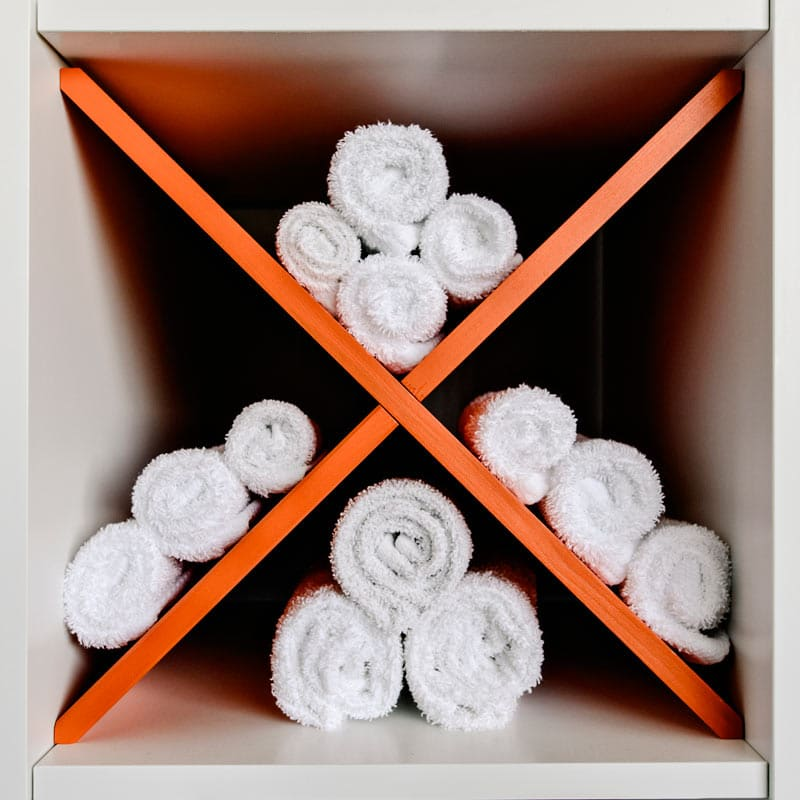 A selection of towels rolled up in a cubby