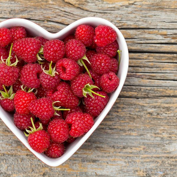 A heart-shaped bowl of raspberries