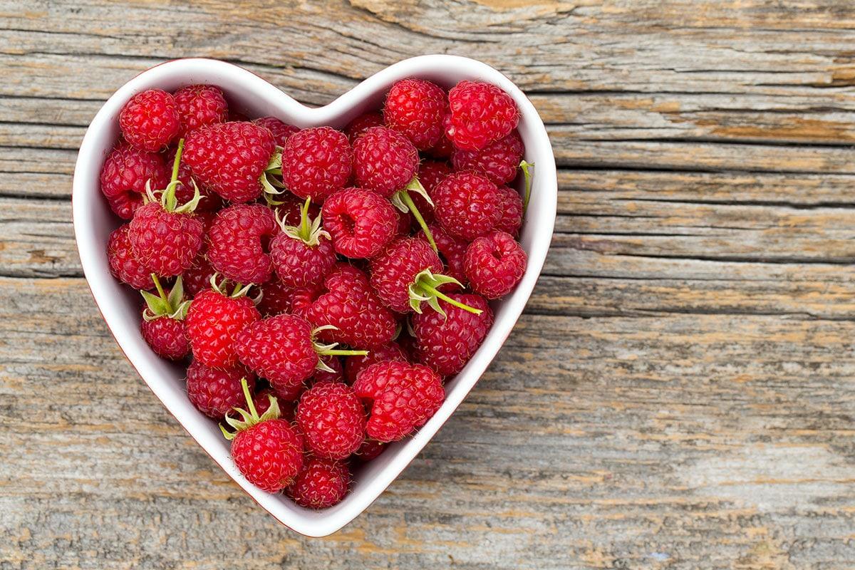 A heart-shaped bowl of raspberries