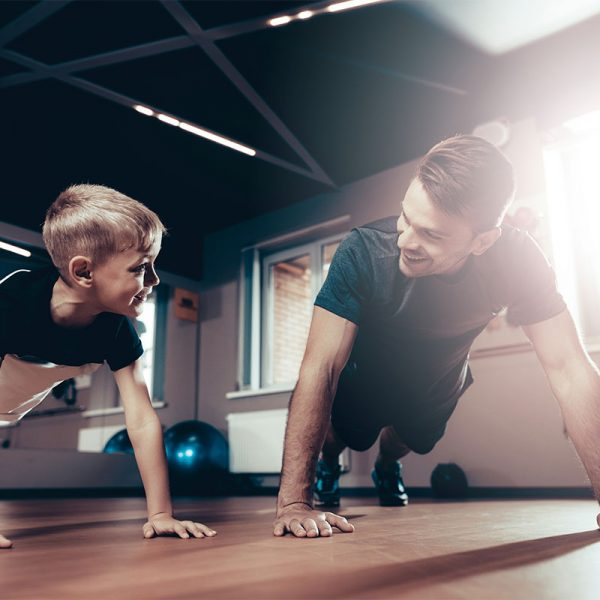 A man and boy exercising together in a gym