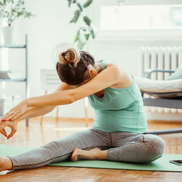 A woman stretching in her living room.