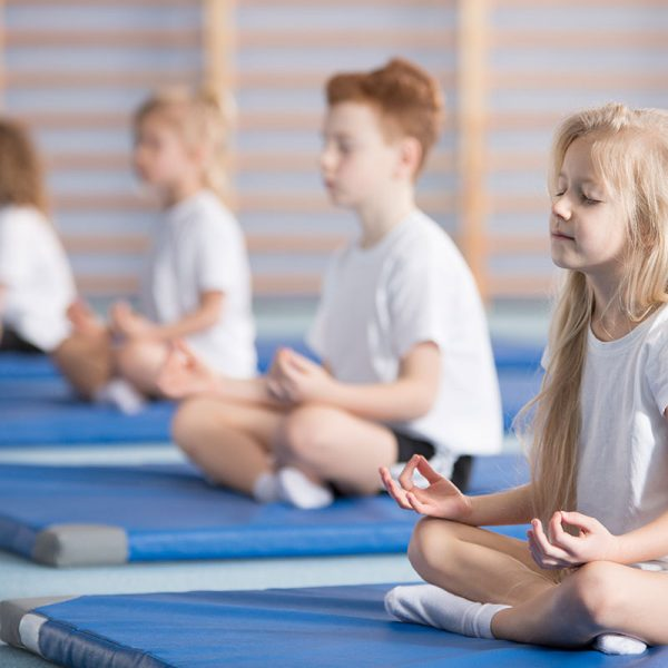 Children meditating on mats.