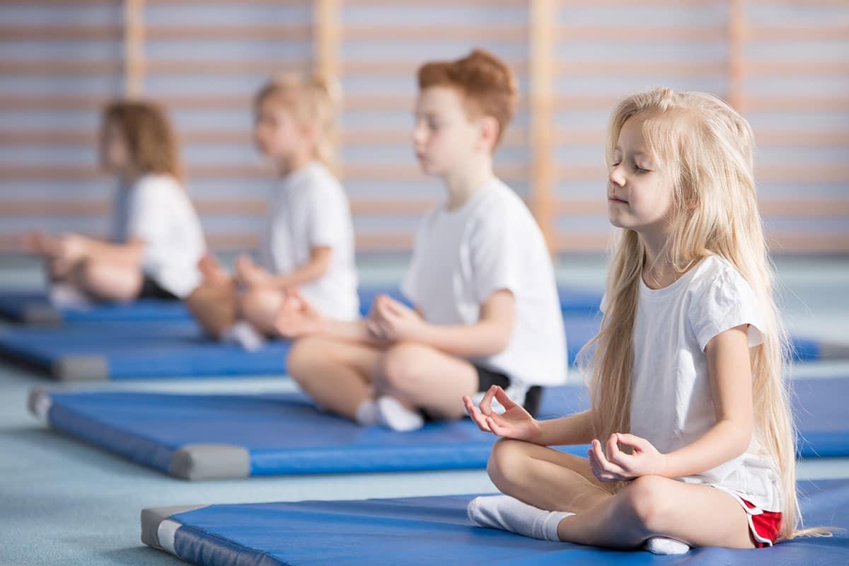 Children meditating on mats.