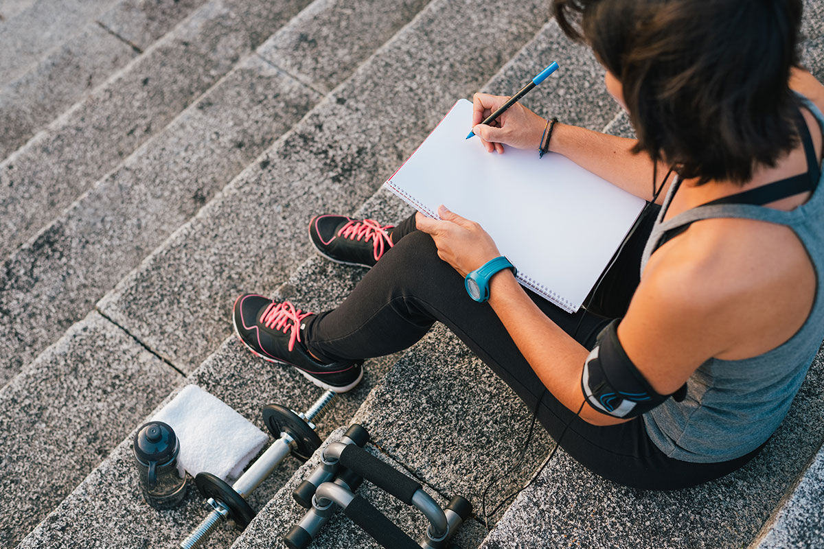 A woman writing in a journal before starting her workout