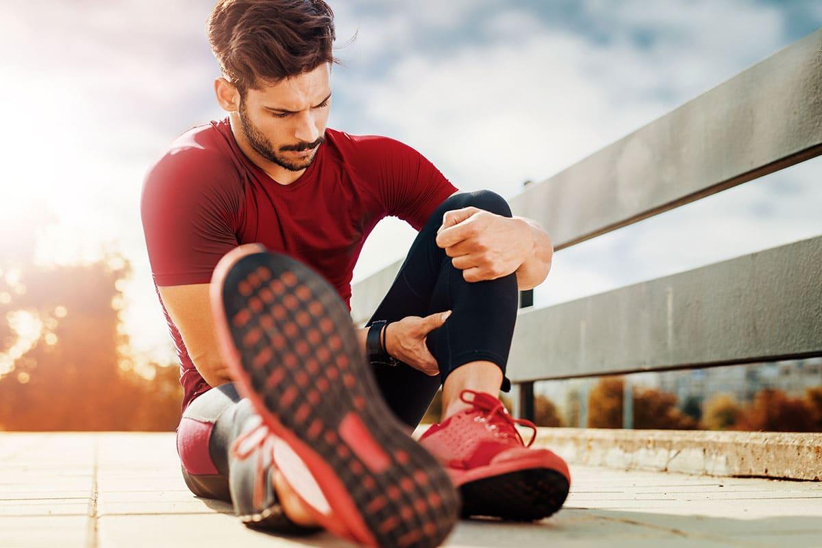 A runner sitting a rubbing a sore calf muscle