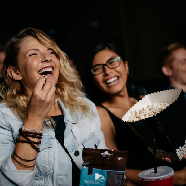 Women laughing in a movie theatre