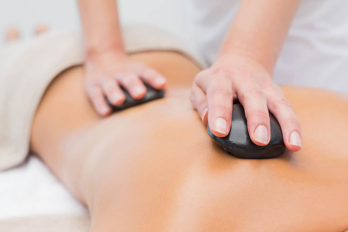 Woman receiving a massage from a therapist using hot stones