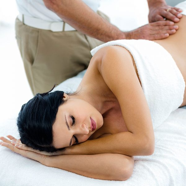 A pregnant woman lying on her side, and receiving a massage.