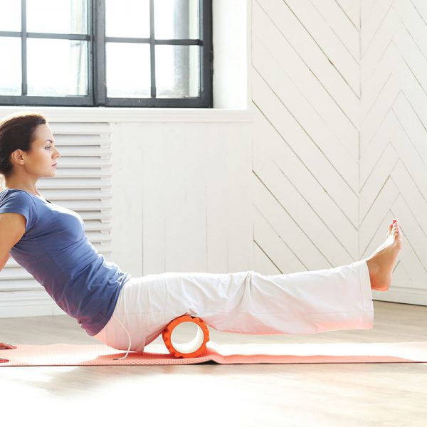 A woman using a foam roller on her hamstrings