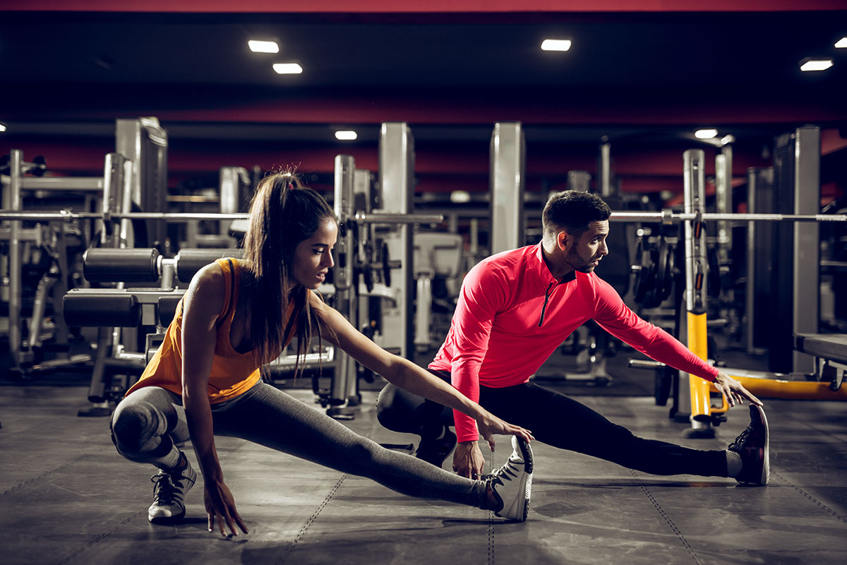 A man and woman doing stretches in a gym.