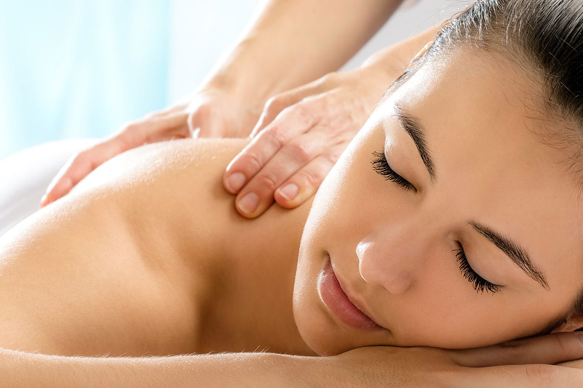 A smiling woman receiving a massage