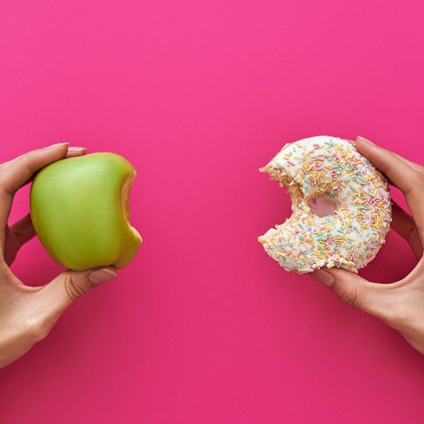 A person holding an apple and a donut on a pink background
