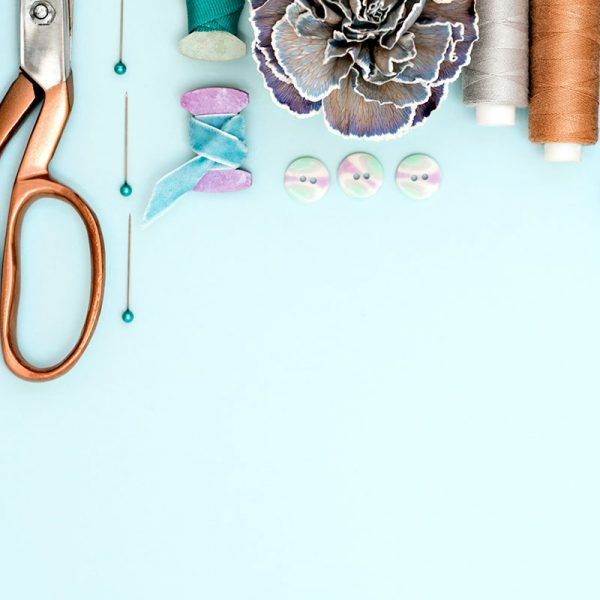 A collection of sewing tools and supplies on a blue background