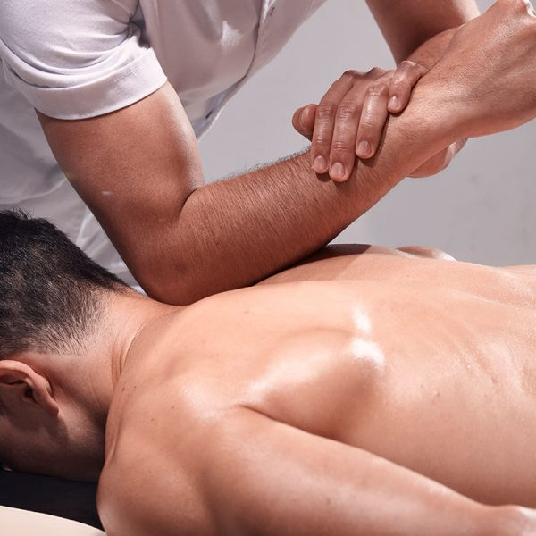 A man receiving a deep tissue massage from a RMT