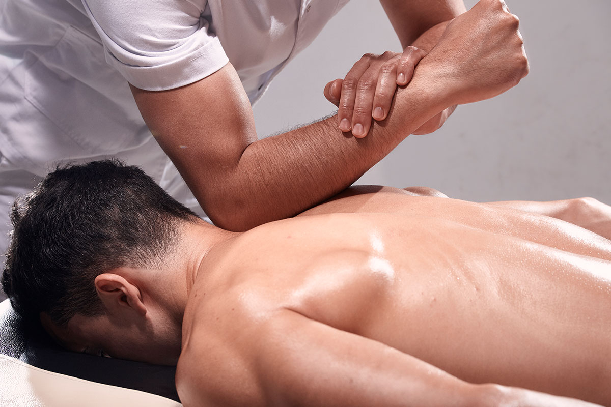 A man receiving a deep tissue massage from a RMT