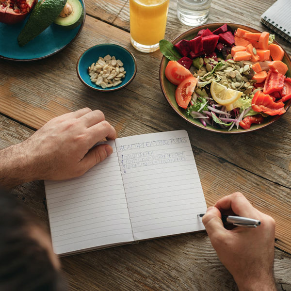 Someone using a journal while eating a healthy meal